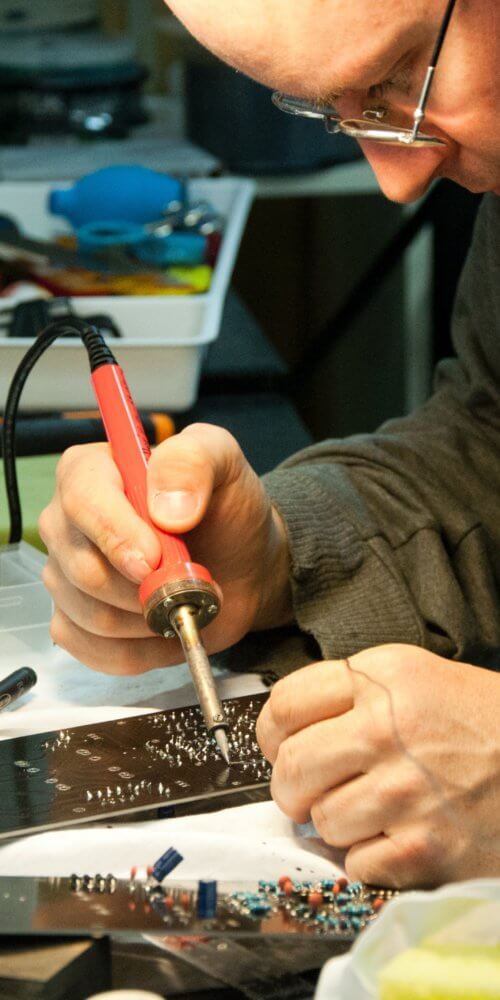 man soldering circuit board